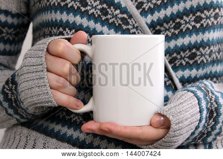 Girl in a warm cardigan is holding white mug in hands. Mockup for winter gifts design.
