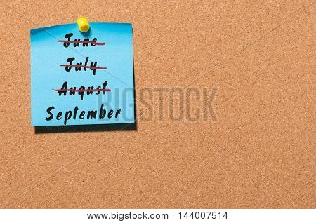 September start and summer end concept written on sticker pinned on notice board. Striked June, July, August.
