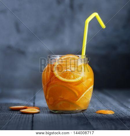 Lemonade with orange in glass jar on old wooden boards. Rustic style, bokeh