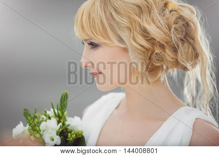 Portrait of a young beautiful bride smiling looking afar holding wedding bouquet outdoors on gray background. Professional make-up and hair-style. Side view.