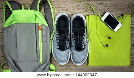 Set for sports shoes, backpack, t-shirt, mobile phone with headphones close-up on a wooden background, top view.