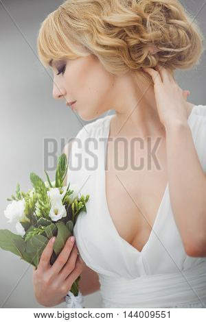Portrait of a young beautiful bride with closed eyes gently embraces wedding bouquet and touching her hair outdoors on gray background. Side view. Professional make-up and hair-style.