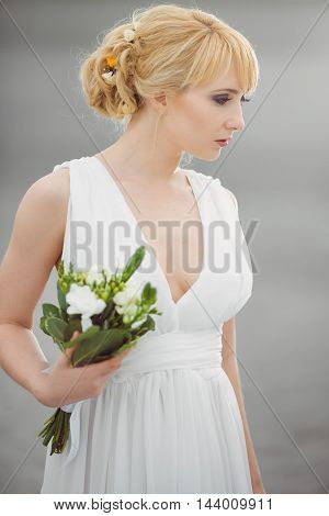 Portrait of a young beautiful bride looking afar gently embraces wedding bouquet outdoors on gray background. Professional make-up and hair-style. Side view.