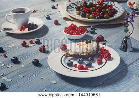 Sweet breakfast with baked pea dessert and berries - red currant, raspberry and bluberries. Beautiful food served at blue rustic wooden table, sweet snack at white porcelain plate, tea cup.