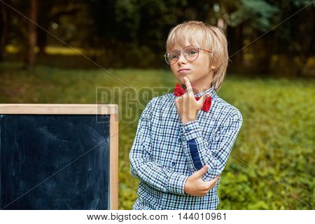 pretty little blond boy with glasses thinking. Back to school concept.