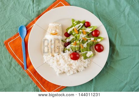 Festive dinner for children - chicken cutlet snowman with rice and salad tree.