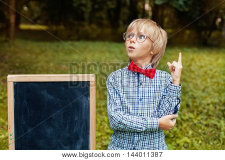 stylish blond little boy with glasses thinking. Back to school concept.
