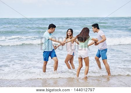 Cheerful Vietnamese friends holding hands and dancing on beach