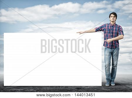 Full length of young handsome man with blank banner pointing on banner with finger