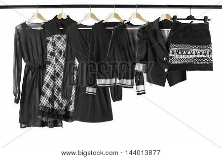 Set of black clothes on clothes racks isolated over white