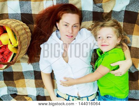 happy young mother and son having a picnic outdoor on a summer day