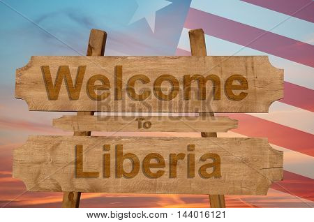Welcome To Liberia Sign On Wood Background With Blending National Flag
