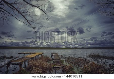 Old wooden pier with dry reed. Cloudy weather. Dramatic sky