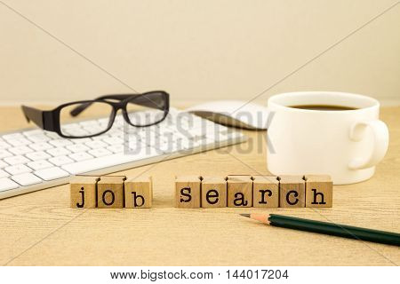 Job search word on rubber stamps place on table with a cup of coffee, keyboard and glasses, concept for employment