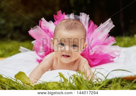 funny little an infant in a pink skirt is
