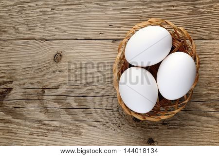 Eggs in small basket on wooden table