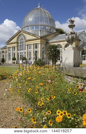 Large Glass House with planted beds in the foreground against a blue summer sky in England