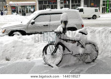 New York City - February 22, 2006: A bicycle and car covered in snow following a winter blizzard