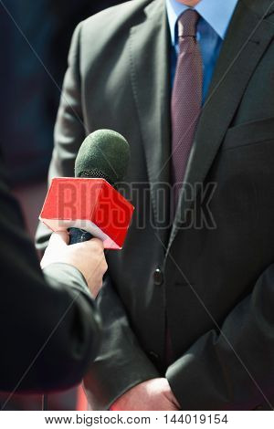 TV reporter interviewing businessman, toned image, close up, unrecognizable people
