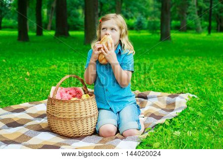 child with a fruit basket and bread outdoor
