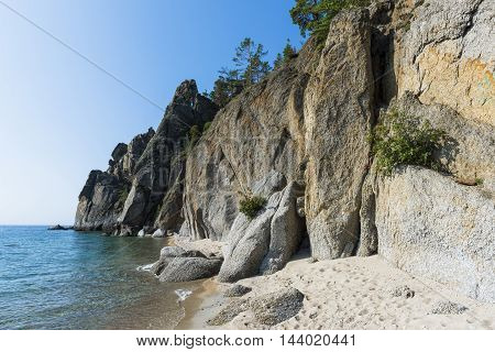Steep cliffs, overgrown with sparse pine trees, break off directly into the waters of lake Baikal.