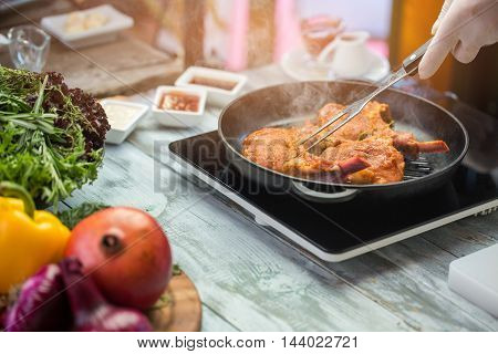 Hand with fork touching meat. Green herbs near frying pan. Chef's recipe of veal ribs. Roast till crust.