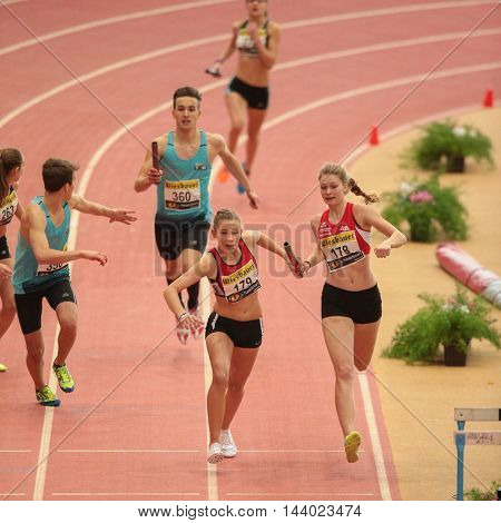 LINZ, AUSTRIA - FEBRUARY 22, 2015: Nancy Illing (#178 Austria) and Tina Simon (#179 Austria)  compete in the women's 4x200m mixed relay event in an indoor track and field event.