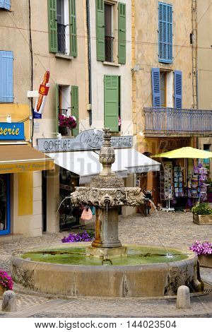 VALENSOLE, FRANCE - JULY 5. 2016: Central square with fountain and private shops at day time