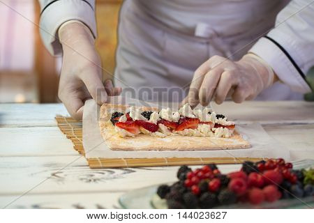 Cream cheese and sliced berries. Chef's hands in rubber gloves. Mascarpone and soft dough. Ingredients for natural dessert.