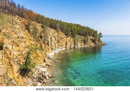 With steep precipitous banks of lake Baikal, the water looks unusual emerald color.