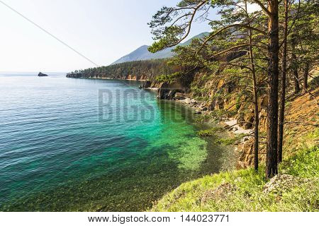 Small bays on the coast of lake Baikal surrounded by high cliffs and filled with emerald water