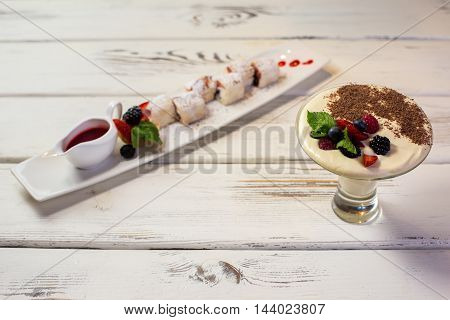 Desserts with berries. Red sauce and chocolate crumbs. Appetizing berry rolls and tiramisu. Sweets in Italian restaurant.