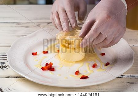 Small cake on white plate. Hands in gloves touch dessert. Chef is decorating creme caramel. Fresh and sweet pudding.
