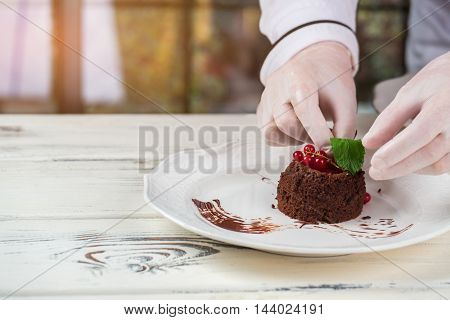 Hands touch dessert on plate. Mint and red currant. Chef prepared chocolate sponge cake. Wooden table with sweet dish.