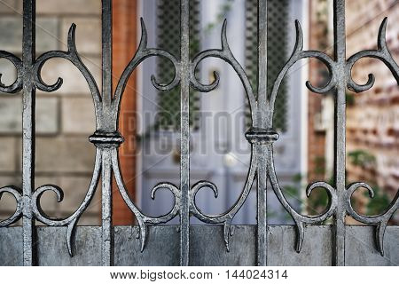 Wrought iron fence fragment in front of a building in Toulouse, France.
