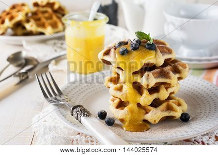 Belgian waffles with lemon Kurd and blueberries. Rustic style. Selective focus.