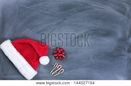 Santa cap gift bow and candy canes on erased chalkboard for Christmas wish list concept.