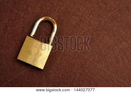 A rusty old pad lock displayed on a brown background
