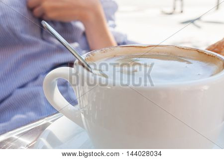 woman hand lower the spoon into the cup of coffee close up outdoor