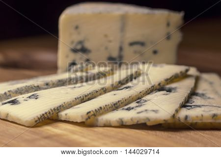 Blue cheese close up on an old wooden boar. Selective focus