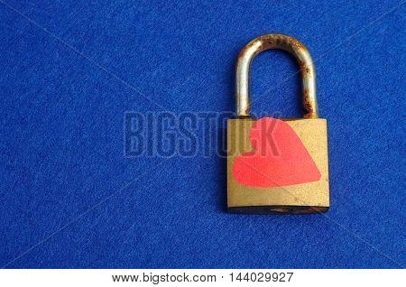 A rusty old pad lock decorated with a red heart displayed on a blue background