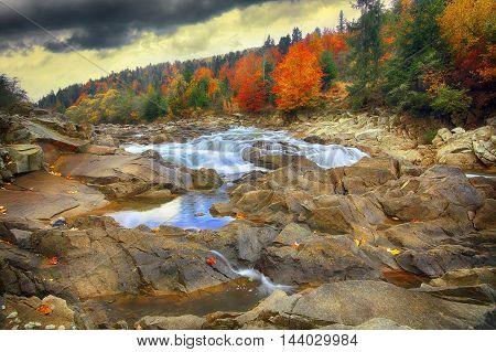 Mountain fast flowing river stream of water in the rocks at autumn time. Colourful foliage