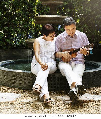 Senior Couple Fountain Ukulele Instrument Concept