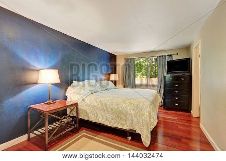 Deep Blue Contrast Wall In Bedroom With Wood Flooring