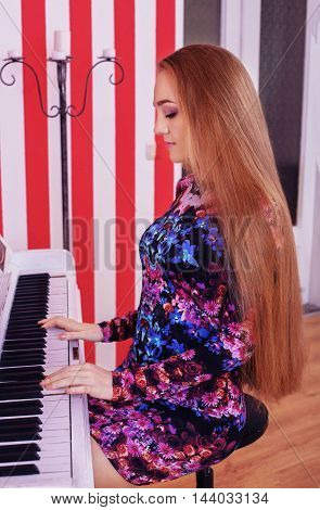 beautiful woman with very long hair playing the piano