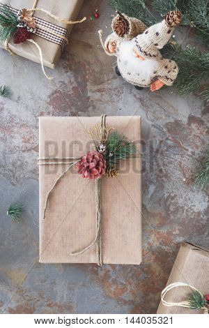 Christmas background with presents and Santa Claus doll figurine on rustic background. Top view, vintage toned image, blank space