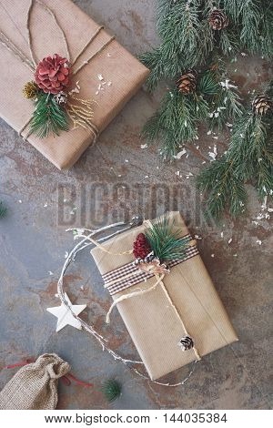 Still life of homemade wrapped Christmas presents with fir tree and pine cone on rustic surface. Top view, vintage toned image, blank space