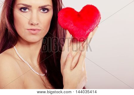 Woman brunette long hair girl holding red heart love symbol studio shot on gray. Valentines day happiness concept