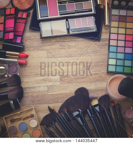 Frame of brushes, lipsticks, maskara, eye shadows and powder on wood, top view , retro toned