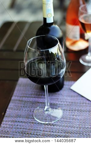 Wine bottle, high wineglass and restaurant menu drink list on the napkin and wood table,